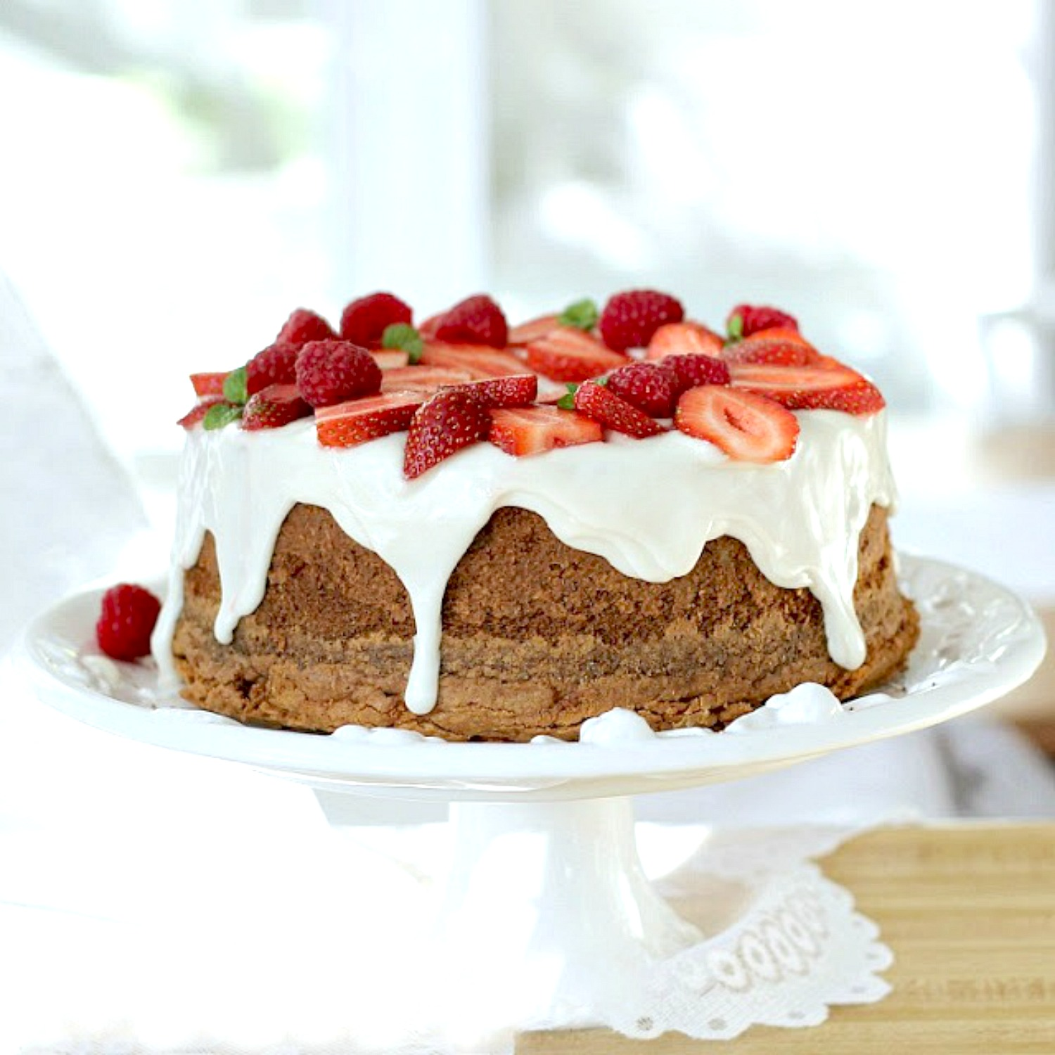 Cream cheese pound cake with snowy white frosting topped with strawberries for a beautiful dessert.