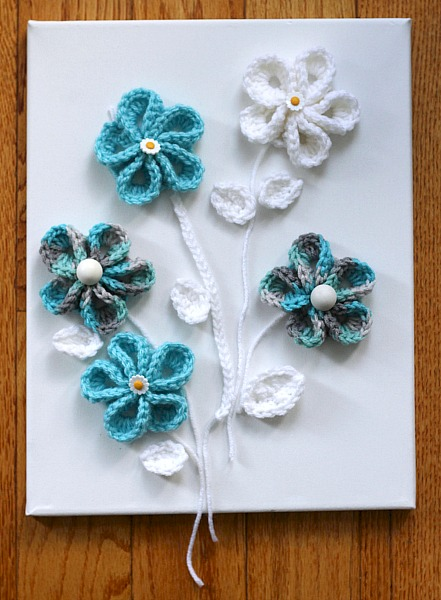Pretty crochet flowers for all kinds of projects. Wall art or embellishing hats, beanies and bags. Easy to follow video tutorial.