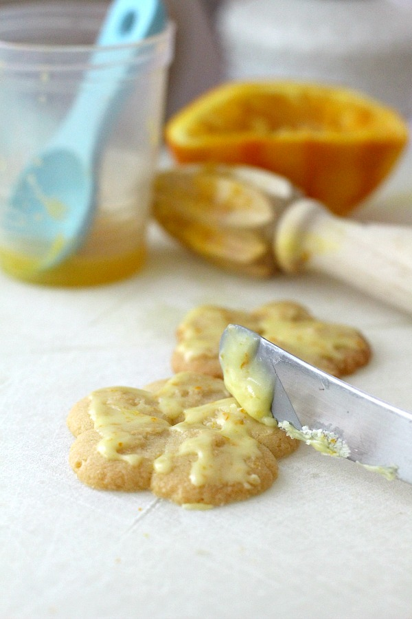 Frosted orange crisps are cookies flavored with orange in the dough and topped with a light orange frosting. They are crisp, tender and the citrus provides a nice surprise in each bite. Made using a cookie press similar to spritz or shortbread cookies but are sweeter. Perfect with a cup of tea, coffee or glass of milk.