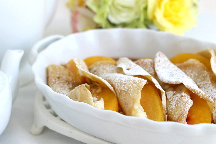 Peaches and Cream Cheese Crepes begins with a simple crepe, then filled with a sweetened cream cheese mixture, fresh sliced peaches, a sprinkling of brown sugar and a pat of butter that is then baked until warmed through. A dusting of confectioners' sugar and topped with whipped cream finishes this lovely dessert.