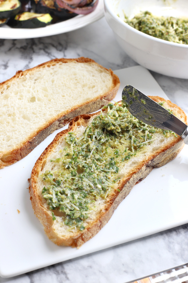 spreading fresh pesto basil on bread for grilled vegetable panini