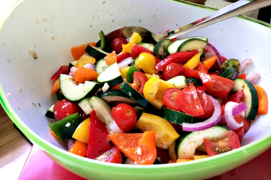 Colorful Greek panzanella salad combines the seasons freshest ingredients with a vibrant and delicious vinaigrette and topped with feta a crispy croutons.