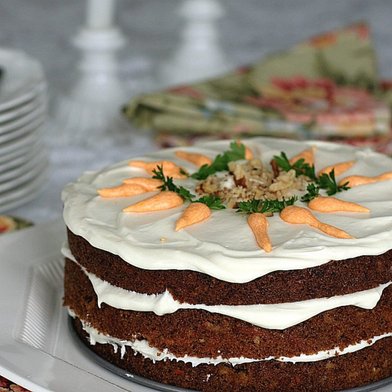 Classic three-layer carrot cake with cream cheese frosting is incredibly moist and delicious! Flecks of carrot, nuts and lightly spiced with cinnamon.