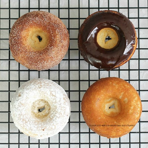 """Debate remains as to how to spell these circular wonders of dough. Spell """"donut"""" or """"doughnut"""", there is no debate about enjoying homemade, donuts. The only decision is whether to choose frosted, rolled in cinnamon sugar, confectioners' sugar or a perfectly plain doughnut. Skip the frying with this easy baked version."""
