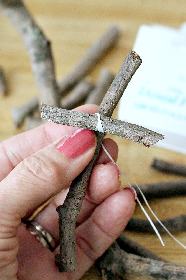 """Make a humble little wooden cross from sticks gathered from your yard. Attach a tag with the bible verse from Luke 2:11, """"a Savior has been born to you"""", as you celebrate Easter or Christmas. These little stick crosses are a sweet and easy holiday craft to make for or with kids."""