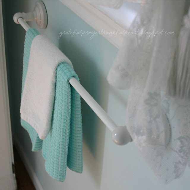 Easy DIY Powder Room redo in Aqua frost paint color with pretty white accents found around the house and re-purposed to create a lovely room on a budget.