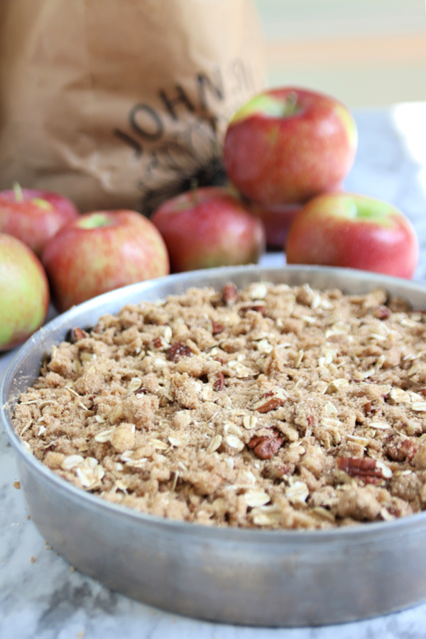 adding the crumb topping to the apple coffee cake batter