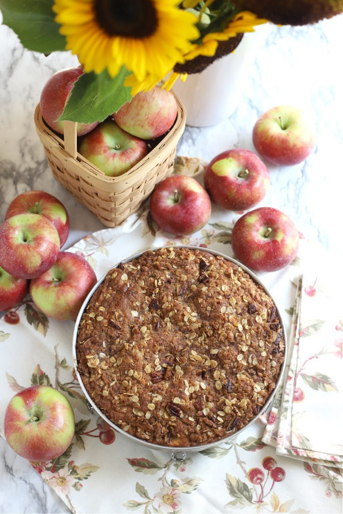 An easy recipe for apple coffee cake with an oat and pecan crumbly topping and a white glaze. It is a lovely autumn dessert or snacking time treat.