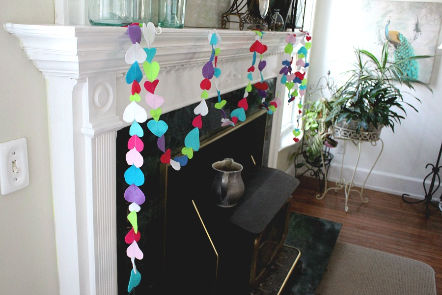 Easy Valentine's Day garland made by sewing felt hearts together. Hang hearts overflowing garland on the mantle, a window or wherever happy hearts are wanted.