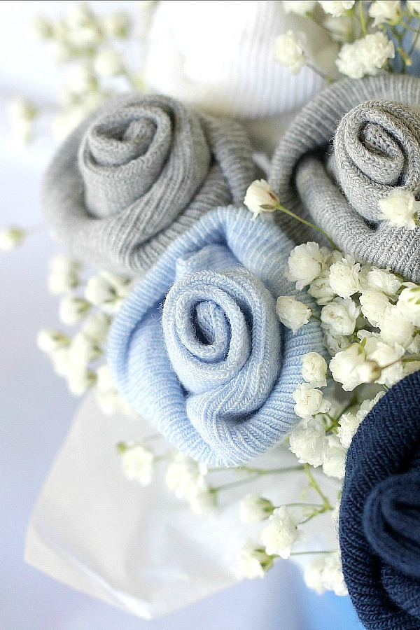 Celebrate a new baby with a sweet baby sock bouquet. Easy how-to tutorial to create a sweet shower decoration or gift for a new mom with little rosebuds from rolled baby socks.