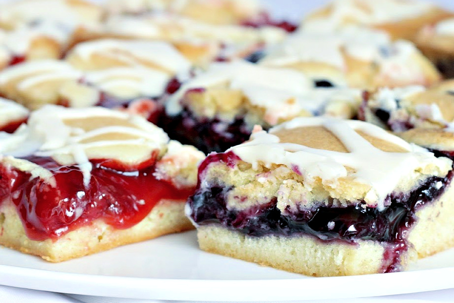 Cherry or blueberry fruit bars are so easy and quick to prepare. Baked in a sheet pan and spread with your favorite pie filling. They are so pretty and appealing. Perfect for breakfast and dessert.