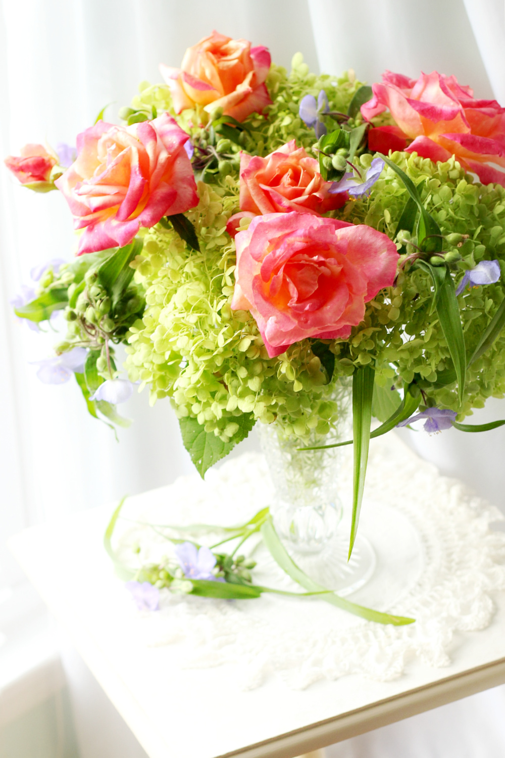 Crystal vase of snowball hydrangea, roses and spiderwort flowers