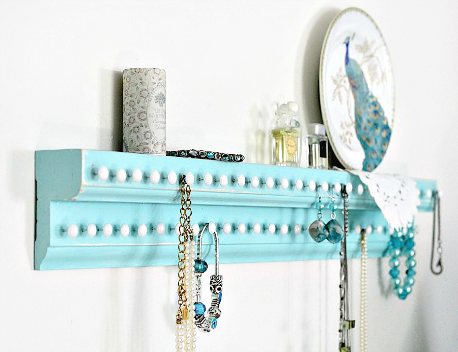 Easy DIY project for keeping jewelry organized and from tangling. Wooden wall shelf has plenty of hooks to keep necklaces and bracelets neat and within easy reach.
