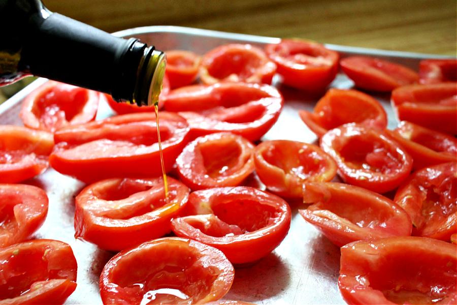 Adding olive oil to Roma tomatoes for roasted tomato Capresse salad