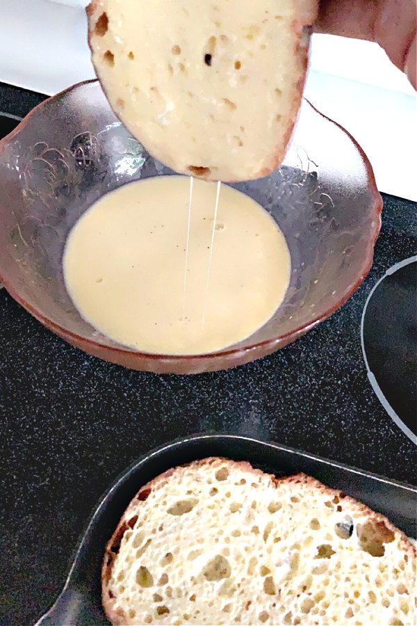 dipping bread into egg mixture for French toast breakfast
