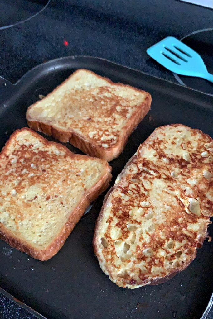 frying egg dipped bread for French toast breakfast