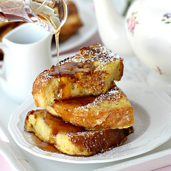 Thick slices of French Toast dusted with confectioners' sugar and served with maple syrup and fruit. It is like eating dessert for breakfast!