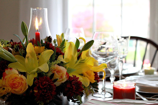 Flowers add a festive touch to your Thanksgiving table. Lovely autumn colors with a hurricane globe & candles creates an elegant tablescape.