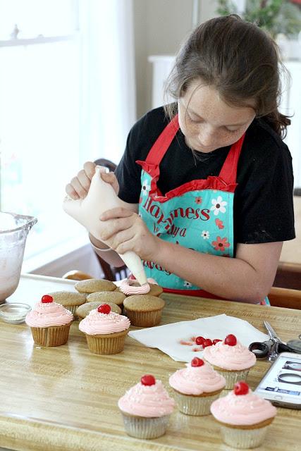 piping cherry frosting onto cupcakes