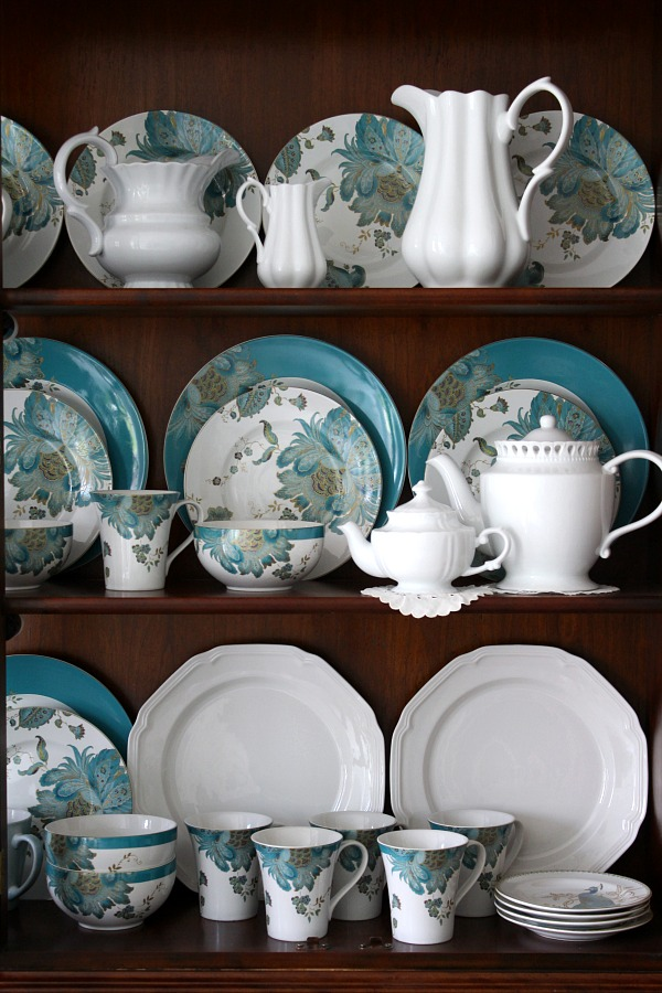 Dining room china cabinet with teal dinnerware dishes from 222 Fifth aqua and teal peacock pattern.