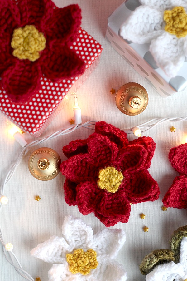 Decorate gifts, wreaths, sew to hats, pillows, or hang as ornaments pretty crochet poinsettia flowers. Festive for holiday decorating and quick and easy to make.