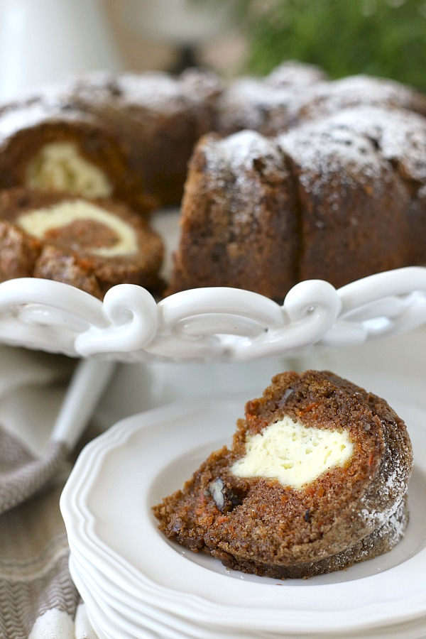 Filled with a tunnel of sweetened cream cheese, surprise carrot bundt cake is moist and delicious dessert. An easy recipe that needs only a dusting of sugar on top.