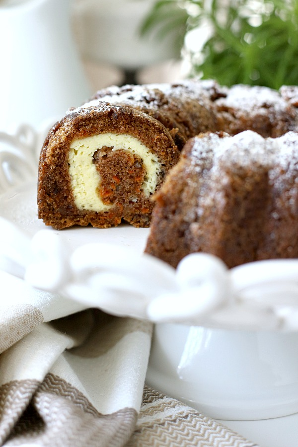 Filled with a tunnel of sweetened cream cheese, surprise carrot Bundt cake is a moist and delicious dessert. An easy recipe that needs only a dusting of sugar on top. A sweet addition to your Easter or brunch table.