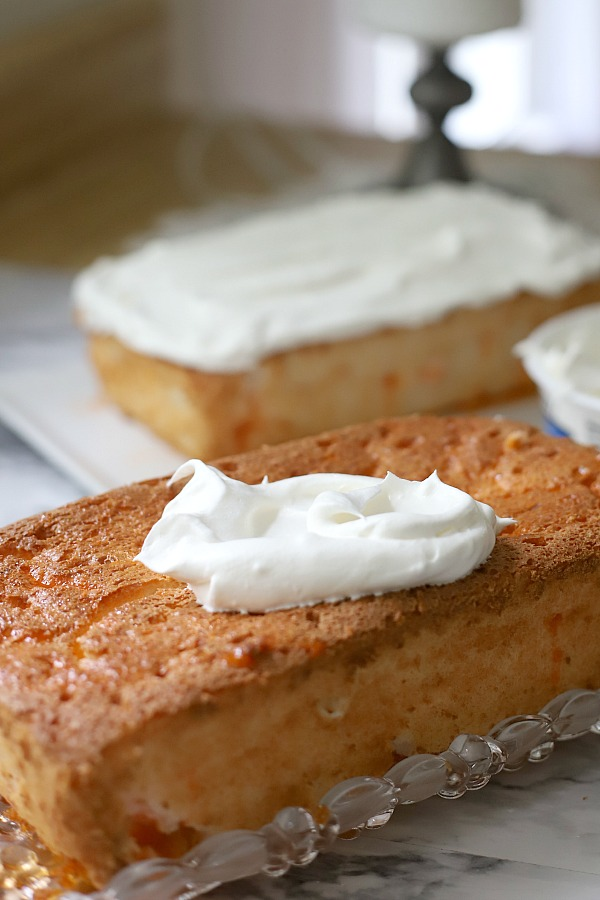 A light dessert and easy recipe for orange angel food cake begins with a box mix. Poke holes throughout the baked cake and pour in Jell-O. Top with whipped topping and serve.