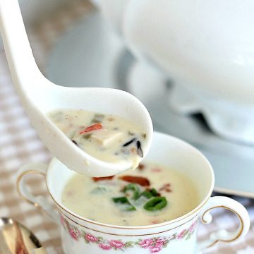 Enjoy a bowlful of creamy chicken wild rice soup with chicken chunks, rice, green onions and bacon! Easy recipe for a special company meal or yummy weeknight dinner.