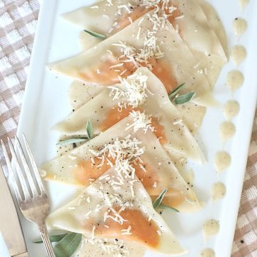 Sweet potato ravioli are prepared with a sweet potato mixture spooned onto wonton wrappers that are folded and simmered briefly in water until tender. Served on a plate with sage infused cream, they are a delicious vegetarian dinner entrée and just right for entertaining or a special occasion meal.