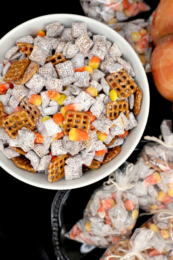 Crunchy, crispy, salty, sweet, Autumn Puppy Chow is easy to make with Chex Mix, chocolate, peanut butter and candy corn. Also called Muddy Buddy it is a perfect Halloween party treat!