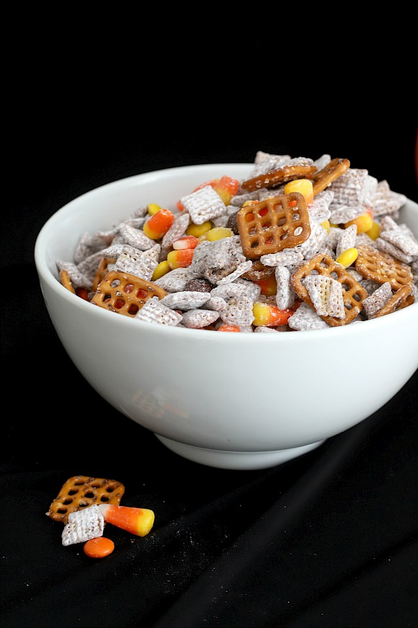 Make a batch of crunchy, crispy, salty and sweet Autumn Puppy Chow for Halloween. Easy recipe for Chex mix Muddy Buddies with chocolate, peanut butter, pretzels and candy corn for a frightfully delicious party treat!