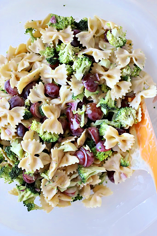 Easy recipe for broccoli grape pasta salad that is tasty, colorful and a perfect side dish or entrée. Tender bow tie pasta is tossed with a creamy, sweet and tangy dressing and topped with toasted pecans and crisp bacon.