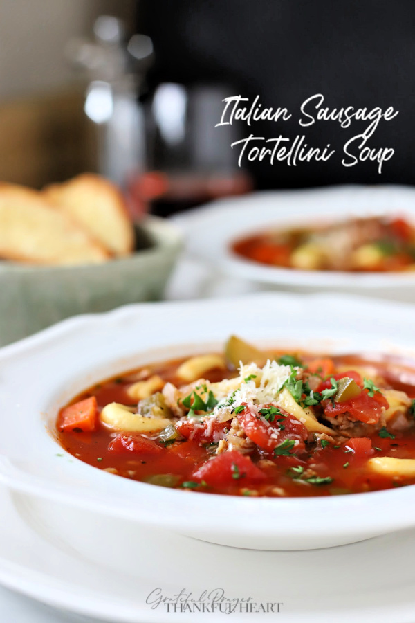 Hearty and so flavorful, this easy recipe for Italian sausage tortellini soup is a meal in a bowl. Elegant for entertaining or perfect for weeknight dinner with crusty bread. Tender veggies and pasta in tomato broth topped with parmesan will warm your soul and tummy.