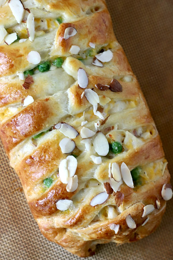 Fancy looking for company brunch or breakfast, crescent chicken braid is baked golden brown with a creamy filling of cheddar cheese and chicken chunks and topped with sliced almonds. Easy recipe using a tube of Pillsbury crescent rolls! A great weeknight family meal too.