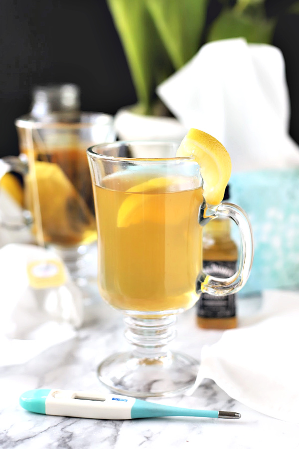 Feel better from cold and flu symptoms with a warm and tasty hot toddy beverage made with bourbon whiskey, tea, honey and lemon, like grandmom used to make.