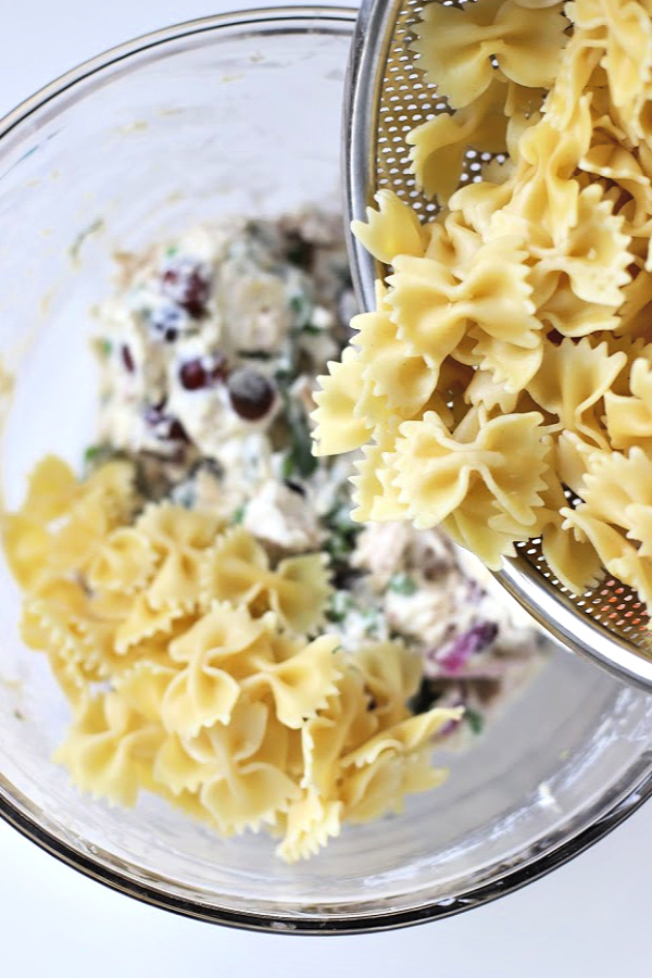 Make a big bowlful of creamy chicken pasta salad for dinner, lunch, potluck or cookout side dish. Easy recipe full of chicken, Parmesan, grapes and veggies with a fresh burst of basil.