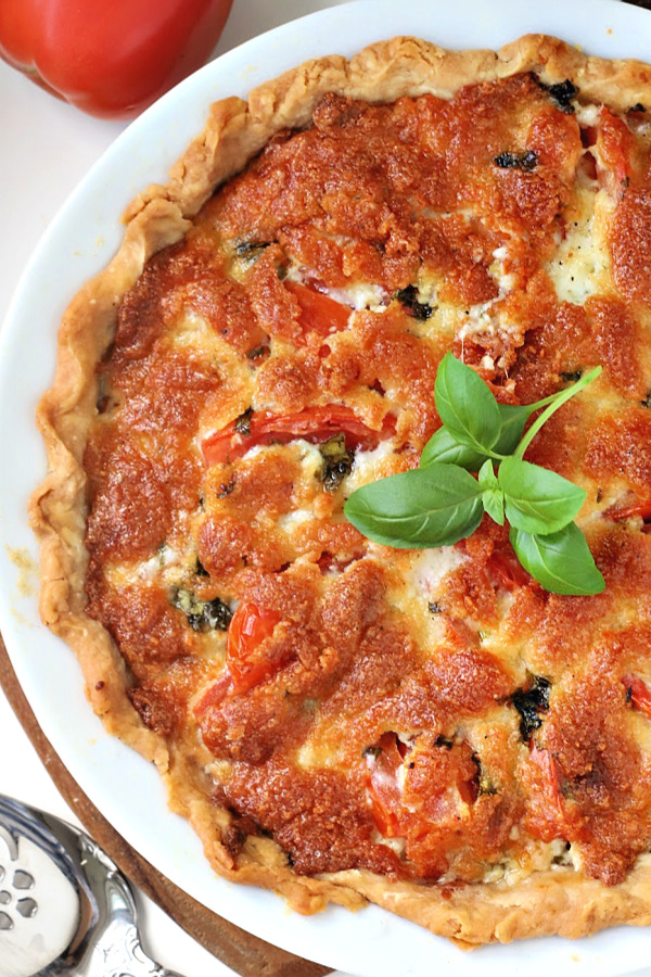 There is something about the flavor combo of fresh tomatoes and basil. Combined with creamy cheese in a flaky crust, basil tomato pie is bright, savory and delicious!