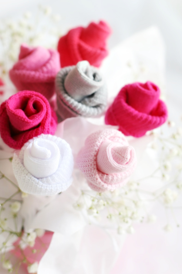 Easy step-by-step how-to for roses from baby socks. DIY rosebud flowers are perfect for shower bouquet and table décor ideas.