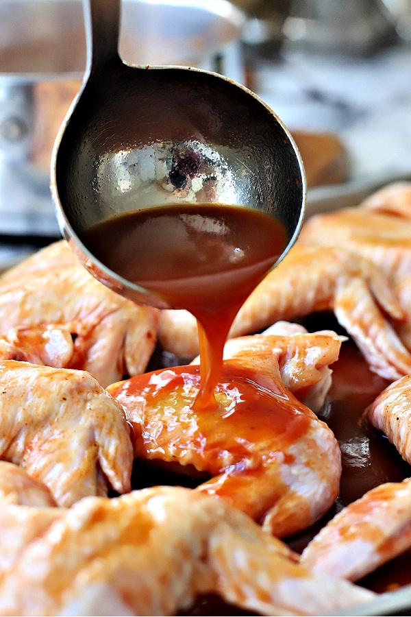 Basting sticky chicken wings with orange glaze