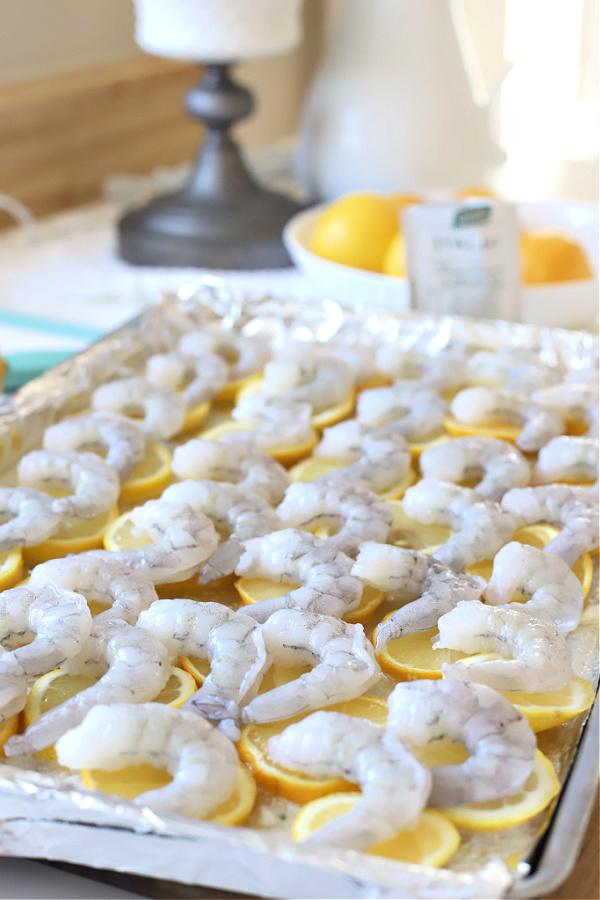 Topping sliced lemons with shrimp for one pan lemon shrimp recipe.