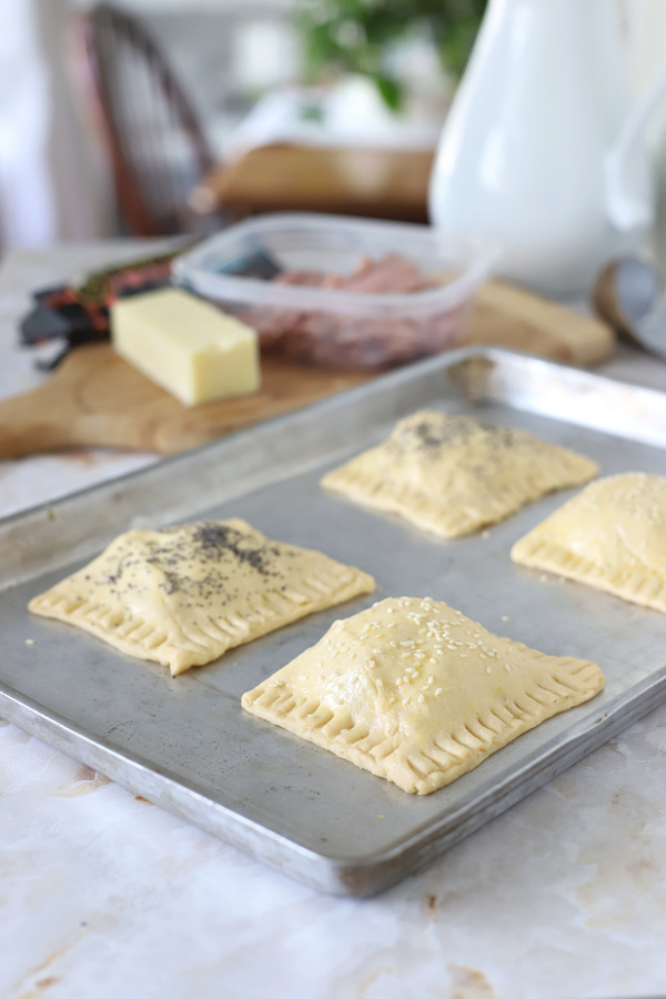 adding poppy and sesame seeds to ham and cheese crescent hand pies