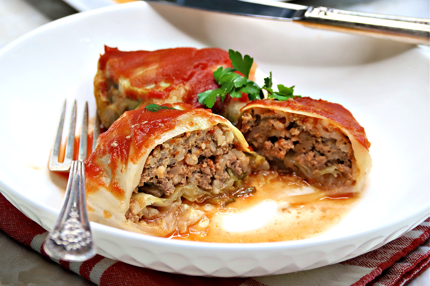 Easy slow cooker recipe for Swedish cabbage rolls filled with ground beef and rice in a tasty sauce is a comforting and satisfying dinner meal.