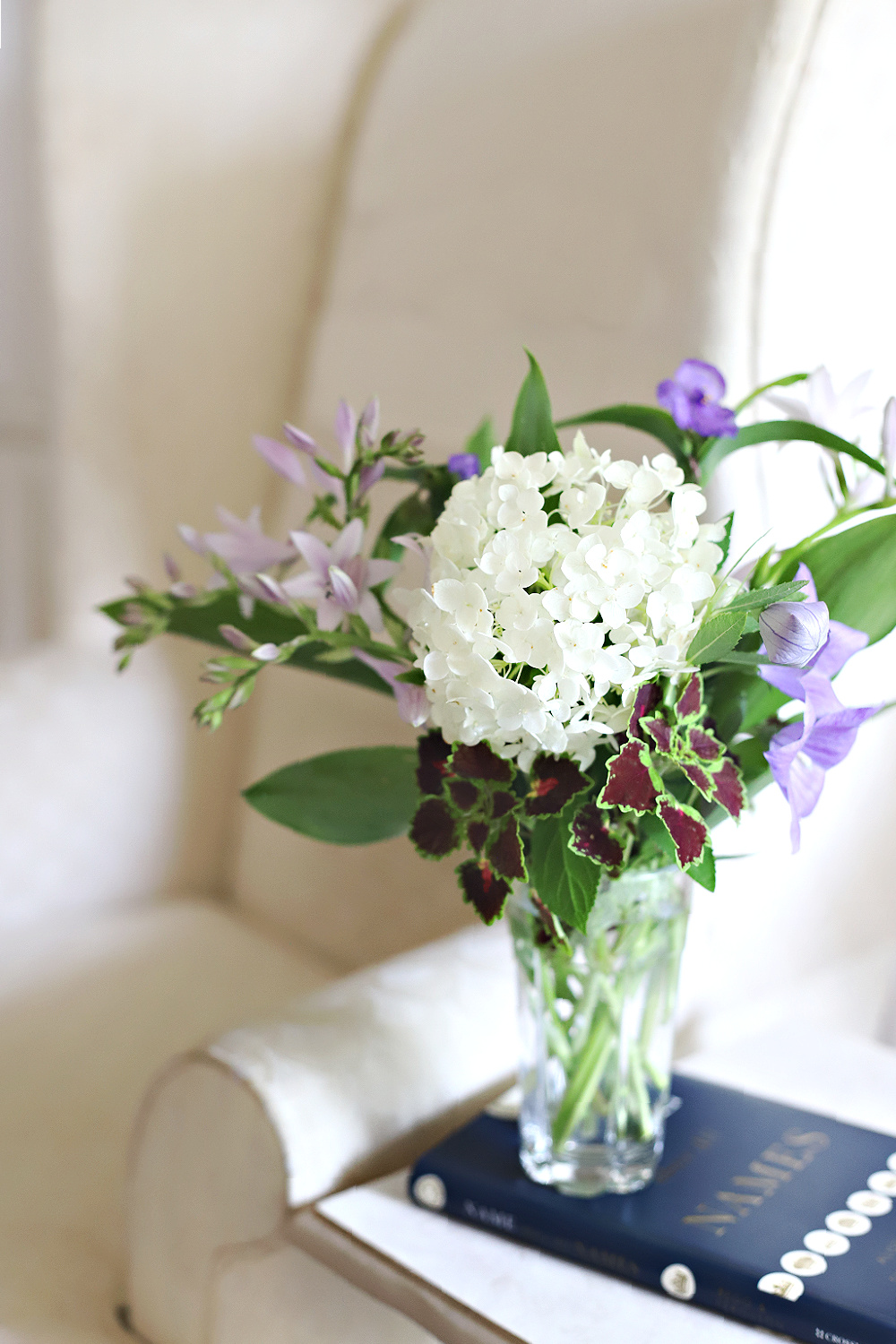 Snippets of flowers gathered after the rain arranged in a vase by the reading chair.
